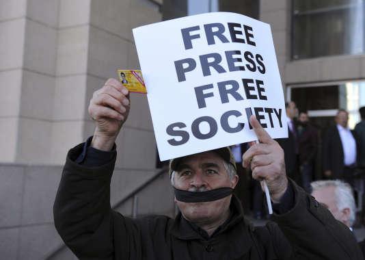 Un journaliste montrant sa carte de presse et portant un baillon manifeste à Istanbul, le 1er avril 2016.