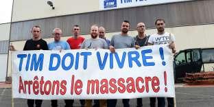 Des employés de TIM devant leur usine.