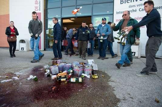 Des viticulteurs français détruisent du vin espagnol devant un supermarché de Caissargues (Gard), le 30 mars.
