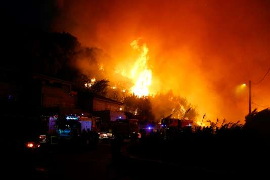 Les pompiers combattent un incendie menaçant des habitations sur la commune de Biguglia (Haute-Corse), le 24 juillet.