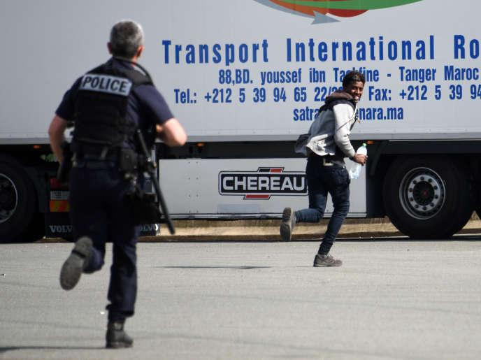 Un policier poursuit un jeune homme soupçonné d'être un migrant, aux abords de Calais (Pas-de-Calais), le 5 juillet.