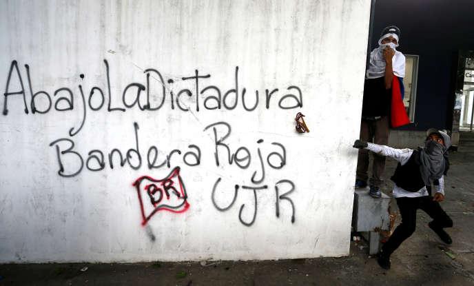 Des manifestants devant un graffiti « A bas la dictature » sur un mur des quartiers est de Caracas lors de la première journée de grève générale le mercredi 26 juillet.