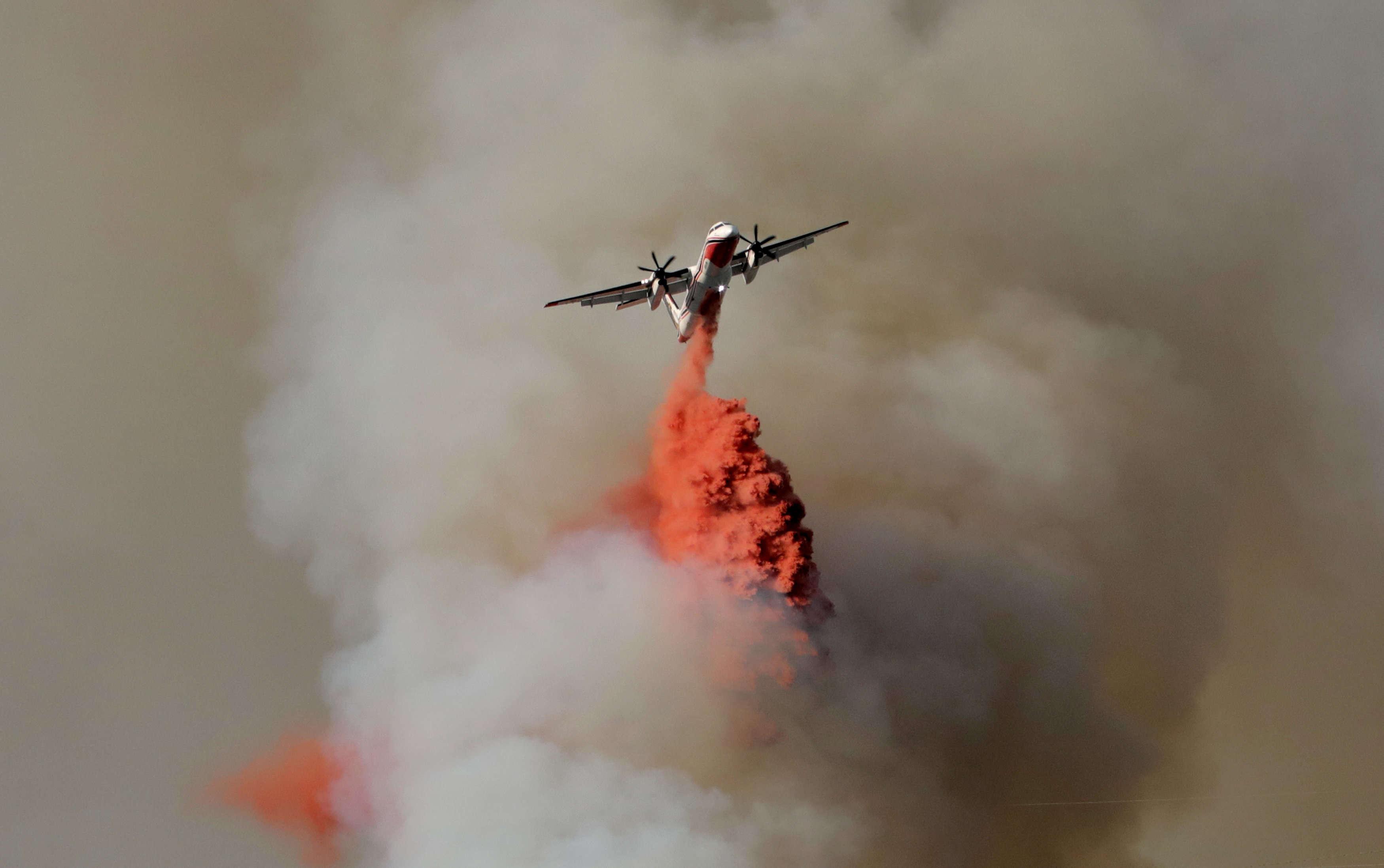 Un Canadair lâche un mélange d'eau et de retardant au-dessus d'une forêt à Castagniers, près de Nice le 17 juillet.