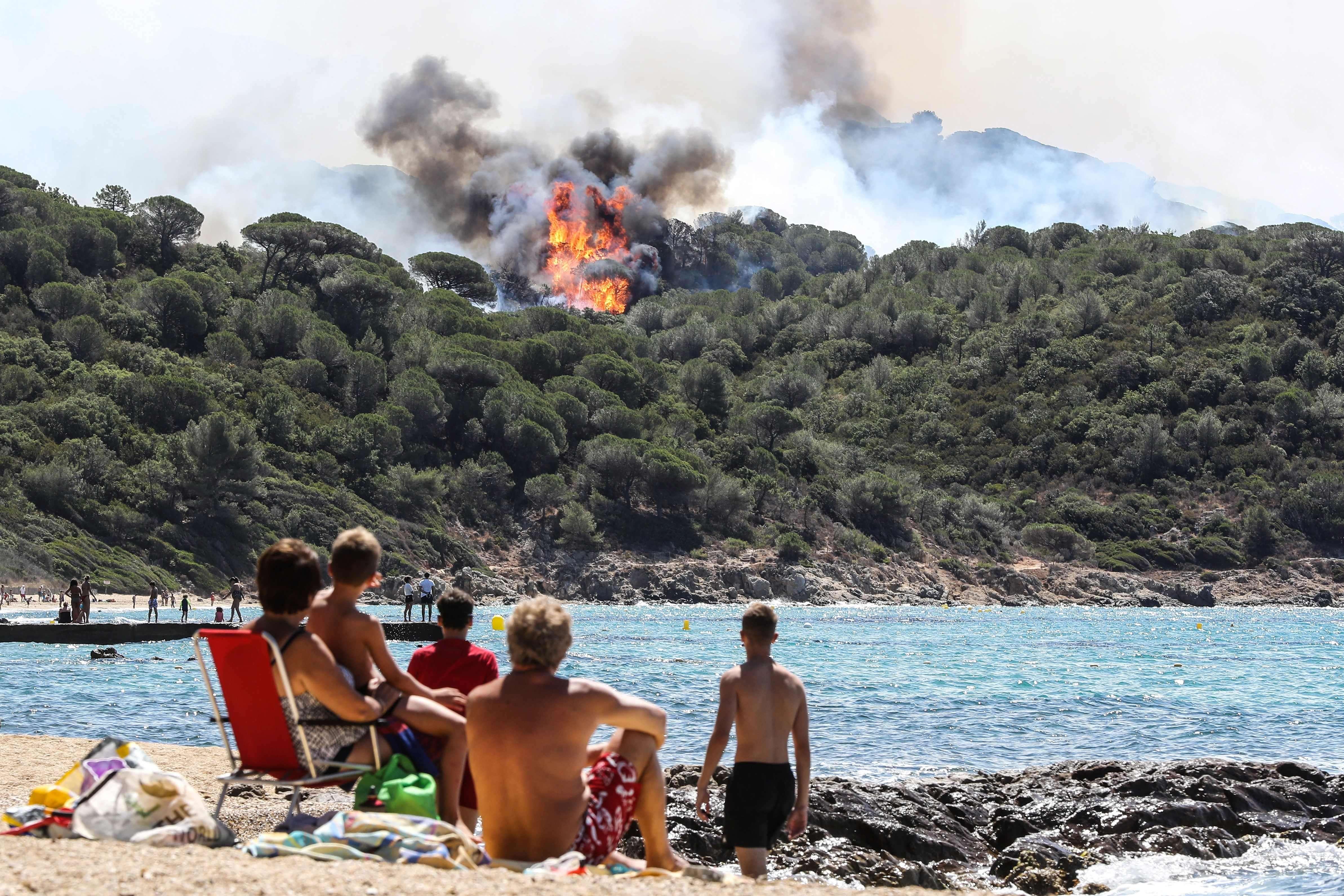 Des vacanciers profitent de la plage face à un incendie dans la forêt de LaCroix-Valmer, près de Saint-Tropez, le 25 juillet.