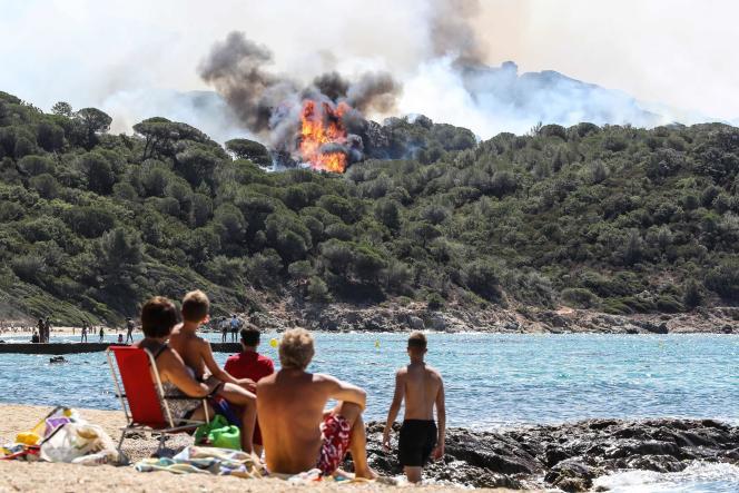 Des vacanciers regardent le feu s'étendre dans la forêt de La Croix-Valmer, près de Saint-Tropez, le 25juillet.