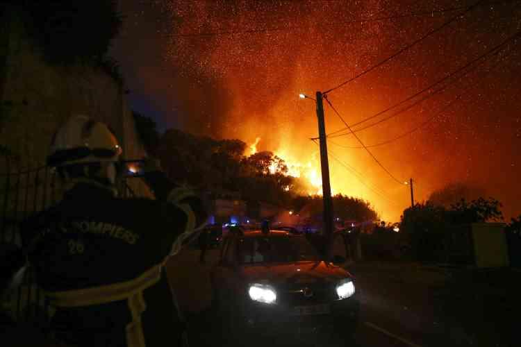 Un pompier prend en photo le ciel en feu avec son téléphone à Biguglia, en Corse, le 24juillet.