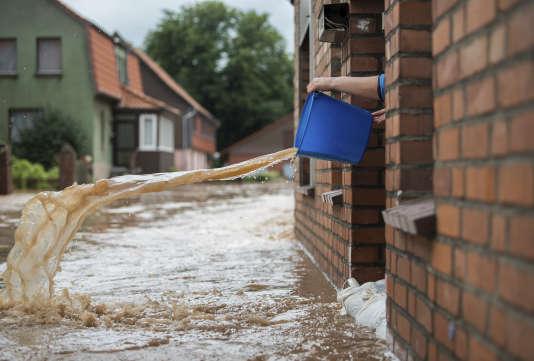 Une habitante de Rhüden, en Allemagne, écope sa maison alors qu'une crue a inondé le village, le 26 juillet.