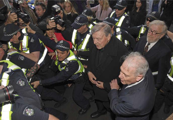 Cardinal George Pell, au centre, entouré par la police alors qu'il arrive au tribunal de Melbourne le 26 juillet 2017.