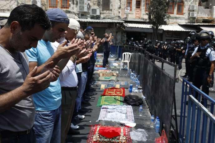 Des Palestiniens prient face aux policiers près de la porte de Damas, à l'extérieur de l'esplanade des Mosquées à Jérusalem (Israël), le 21 juillet.