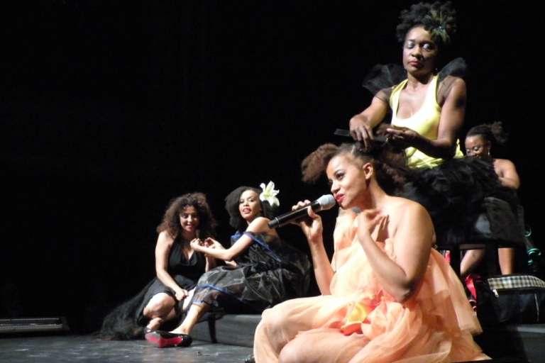 Eva Doumbia au premier plan en train de se faire tisser les cheveux sur scène pour son spectacle de cabaret «Moi et mon cheveu».
