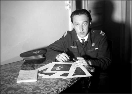 Portrait d'archives daté de novembre 1945, de l'écrivain français Romain Gary, en uniforme militaire, signant des autographes sur ses photos.