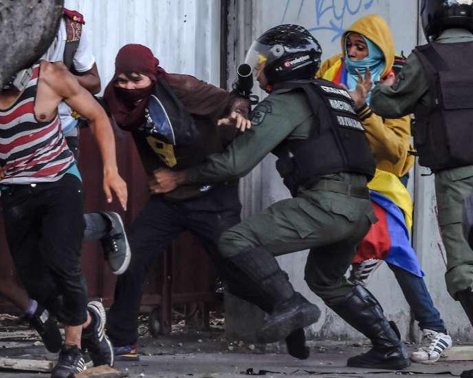 Des membres de la garde nationale vénézuelienne essaient d'arrêter des manifestantsanti-governementaux le 27 juillet 2017 au deuxième jour de la grève générale.