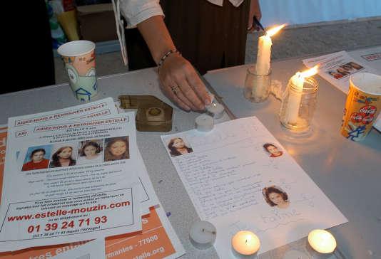 Une personne allume une bougie à proximité d'un poème dédié à Estelle Mouzin disparue depuis le 09 janvier 2003, lors de la journée internationale des enfants disparus, le 25 mai 2004 sur le Champs de Mars à Paris.