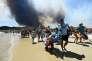 Des vacanciers quittent la plage de Bormes-les-Mimosas (Var), pendant l'incendie le 26 juillet.