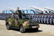 """In this photo released by Xinhua News Agency, Chinese President Xi Jinping stands on a military jeep as he inspects troops of the People's Liberation Army during a military parade to commemorate the 90th anniversary of the founding of the PLA at Zhurihe training base in north China's Inner Mongolia Autonomous Region, Sunday, July 30, 2017. China's military has the """"confidence and capability"""" to bolster the country's rise into a world power, President Xi Jinping said Sunday as he oversaw a large-scale military parade meant to show off the forces at his command to foreign and domestic audiences. (Li Tao/Xinhua via AP)"""