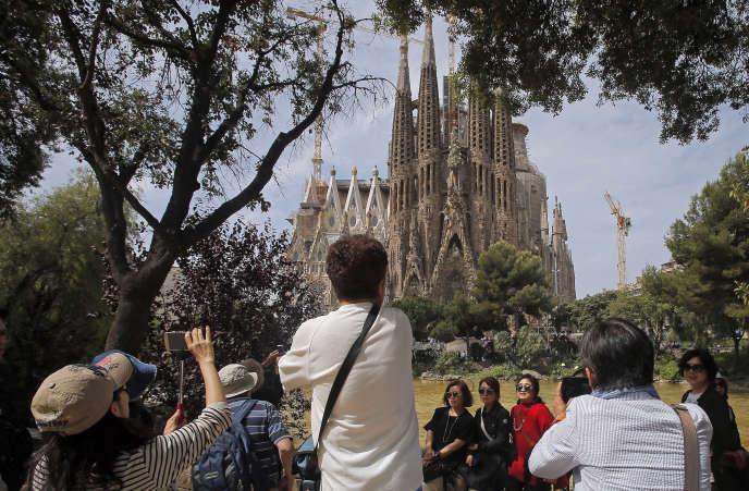 Des touristes prennent des photos, le 26 mai 2016,de la basilique de la Sagrada Familia, conçue par l'architecte Antoni Gaudi.