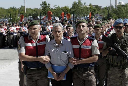 La police paramilitaire turque et des membres des forces spéciales escortent l'ancien commandant de l'armée de l'air Akin Özturk, le 1er août 2017, devant le tribunal chargé de juger les suspects censément impliqués dans le coup d'Etat manqué du15juillet 2016.