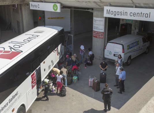 Des demandeurs d'asile déchargent leurs affaires en arrivant au stade olympique de Montréal le 2 août 2017.