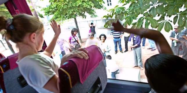 Des enfants font signe à leur parents par la vitre du bus qui les amènent en colonies de vacances, en juillet 2003, à Lyon.