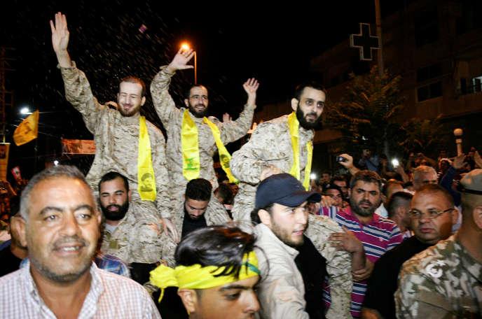 Des combattants du Hezbollah accueillis en héros à leur arrivée à Al-Qaa, en territoire libanais, jeudi 3août, aprèsleur libération par l'ex-Front Al-Nosra.
