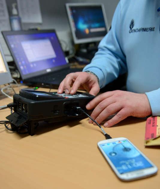 Un gendarme utilise un appareil pour récupérer des données, le 9 janvier 2014 à Arras, dans le nord de la France.