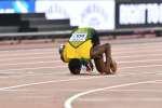 TOPSHOT - Jamaica's Usain Bolt kisses the track after taking bronze in the final of the men's 100m athletics event at the 2017 IAAF World Championships at the London Stadium in London on August 5, 2017. / AFP / Ben STANSALL