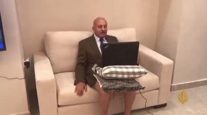 Le journaliste Majid Asfour, costume cravate pour le sérieux et ordinateur sur les jambes nues pour la décontraction.