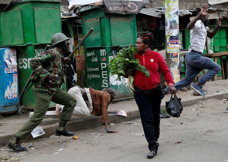 Un policier anti-émeute essaie de disperser des manifestants pendant qu'une femme continue son marché à Mathare, à Nairobi, le 9 août.