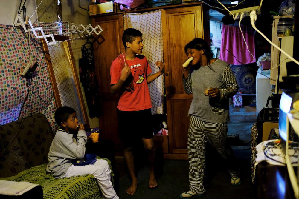 Fabiana avec ses fils, Brian (à gauche), 8ans, et Breno, 14ans, pendant le petit-déjeuner, chez eux, dans la favela de Moinho.