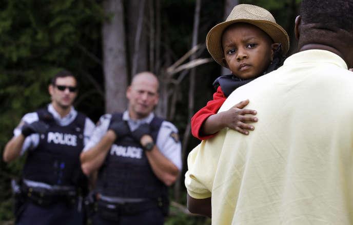 Un enfant haïtien et son père à Saint-Bernard-de-Lacolle, au sud de Montréal, près de la frontière avec les Etats-Unis, le 7 août.