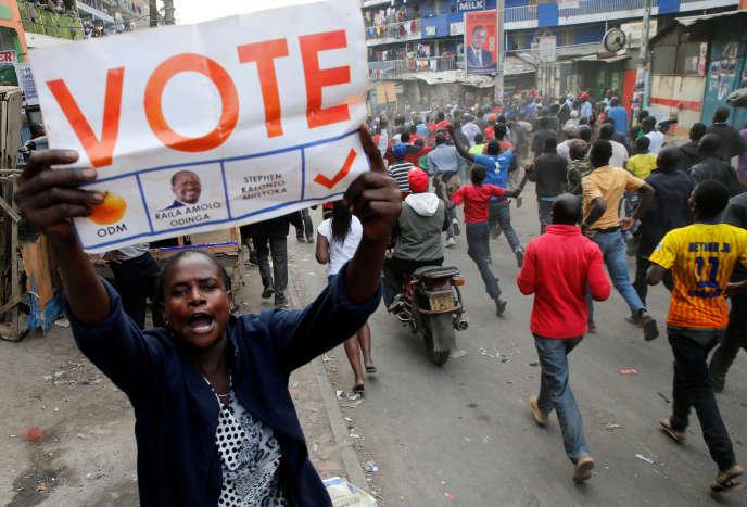 Une partisane du leader de l'oppositionRaila Odinga brandit une pancarte, pendant que d'autres manifestent dans une rue d'Humura, un quartier de Nairobi, au Kenya.