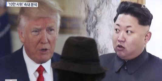 Un homme devant un programme télé montrant le president Donald Trump le leader nord-coréen Kim Jong Undans une gare à Seoul en Corée du Sud le 10 août.