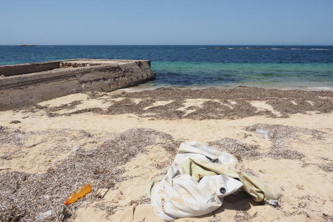 A côté du site archéologique de Sabratha le 20 juillet, un Zodiac blanc est enfoui dans le sable, avec un tas d'habits, des déchets et des bidons d'eau.