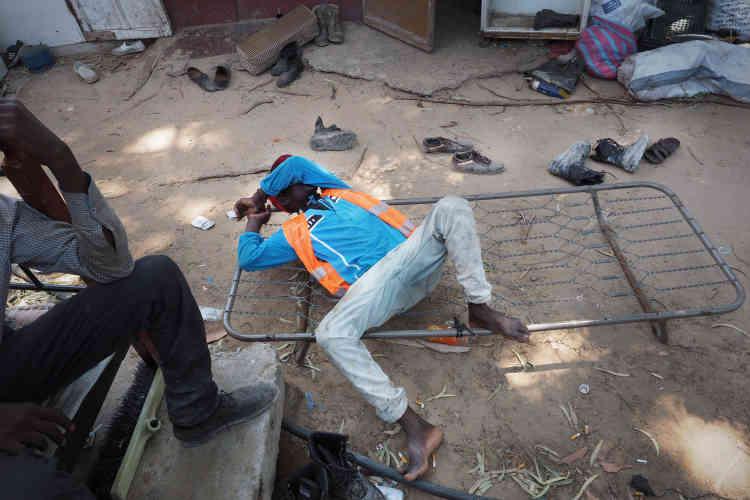 Dans le ghetto pour les collecteurs de déchets, à Tripoli. Cet homme originaire du Niger rentre à peine de sa journée de travail, il s'effondre de fatigue.