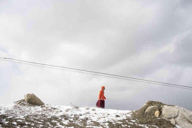 Au bord de la route qui mène à une montagne enneigée, un enfant porte des vêtements monastiques.