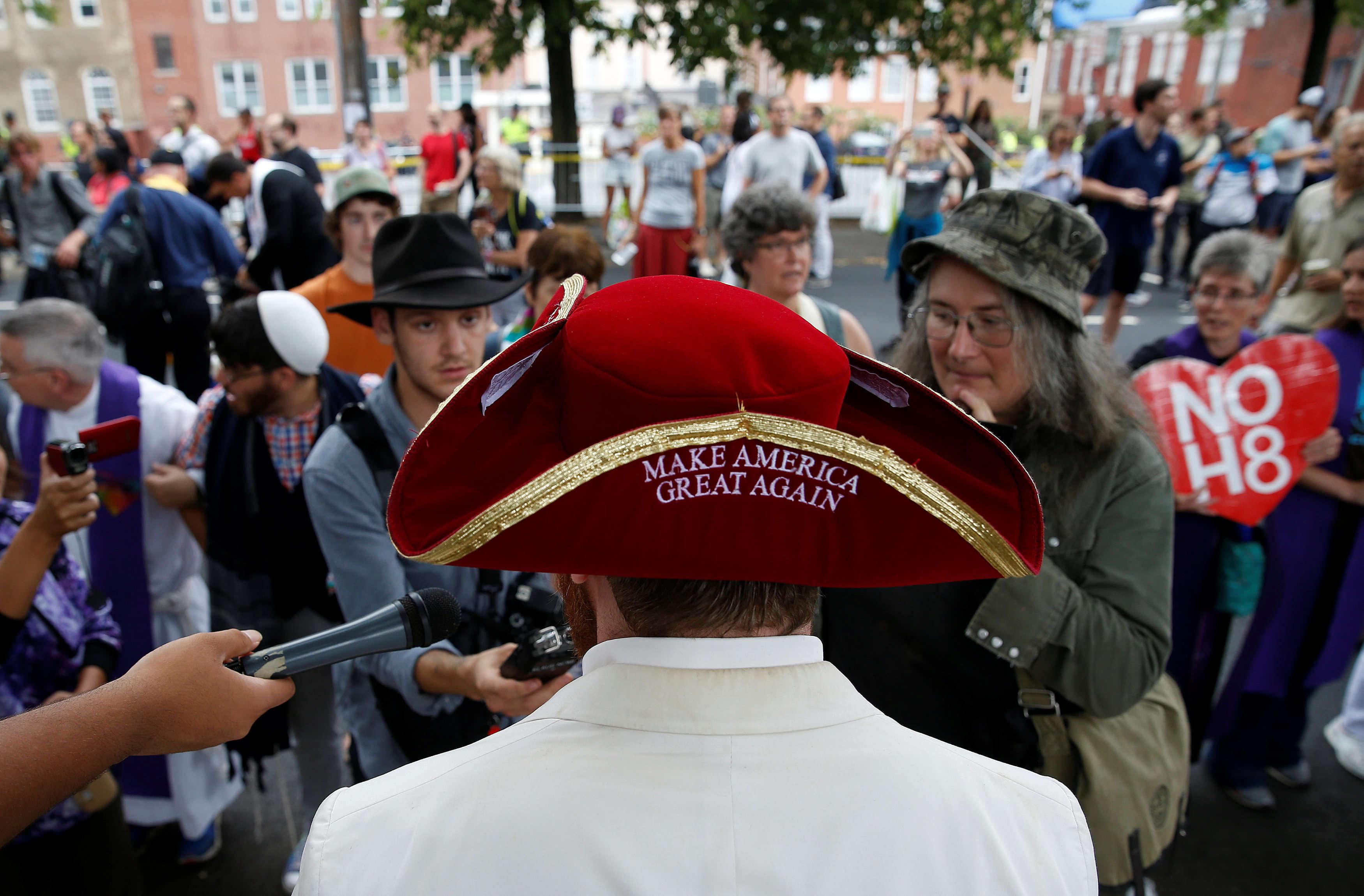 Un suprémaciste blanc répond aux médias, flanqué d'un chapeau colonial où est inscrit le slogan de campagne de Donald Trump : « Make America Great Again».