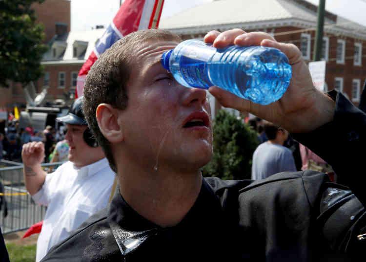 Une suprémaciste blanc se lave les yeux à l'eau après avoir été aspergé de gaz lacrymogène.