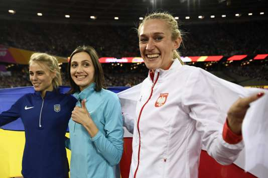 Au centre, Maria Lasitskene n'a pas le droit au drapeau russe. Elle est championne du monde de saut en hauteursous bannière neutre.