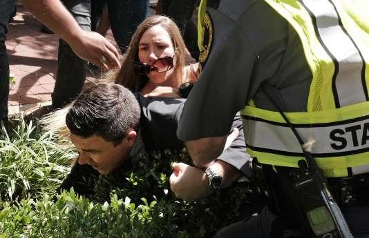 L'organisateur du rassemblement « Unite the Right», Jason Kessler, aidé par la police après avoir été attaqué par une femme pendant sa conférence de presse à Charlottesville (Virginie), le 13 août 2017.