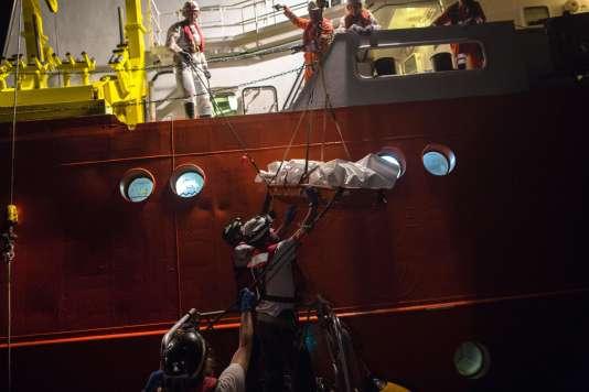 Le cadavre d'un migrant est transféré d'un navire à l'autre pour être acheminé vers un port italien, le 3 août.
