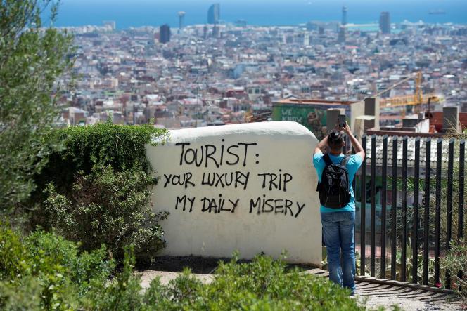 Un graffiti« Touriste : ton voyage de luxe, ma misère quotidienne», au parc Güell, à Barcelone, le 10 août.
