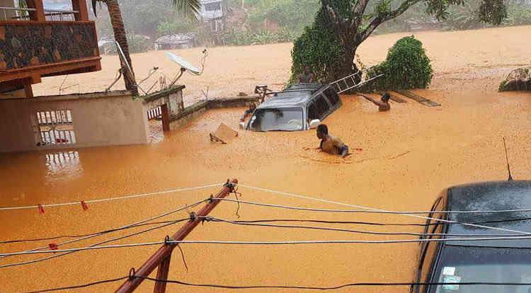 La boue jusqu'aux épaules, un homme se retrouve au milieu des inondations dans les rues de Regent, un quartier de Freetown.