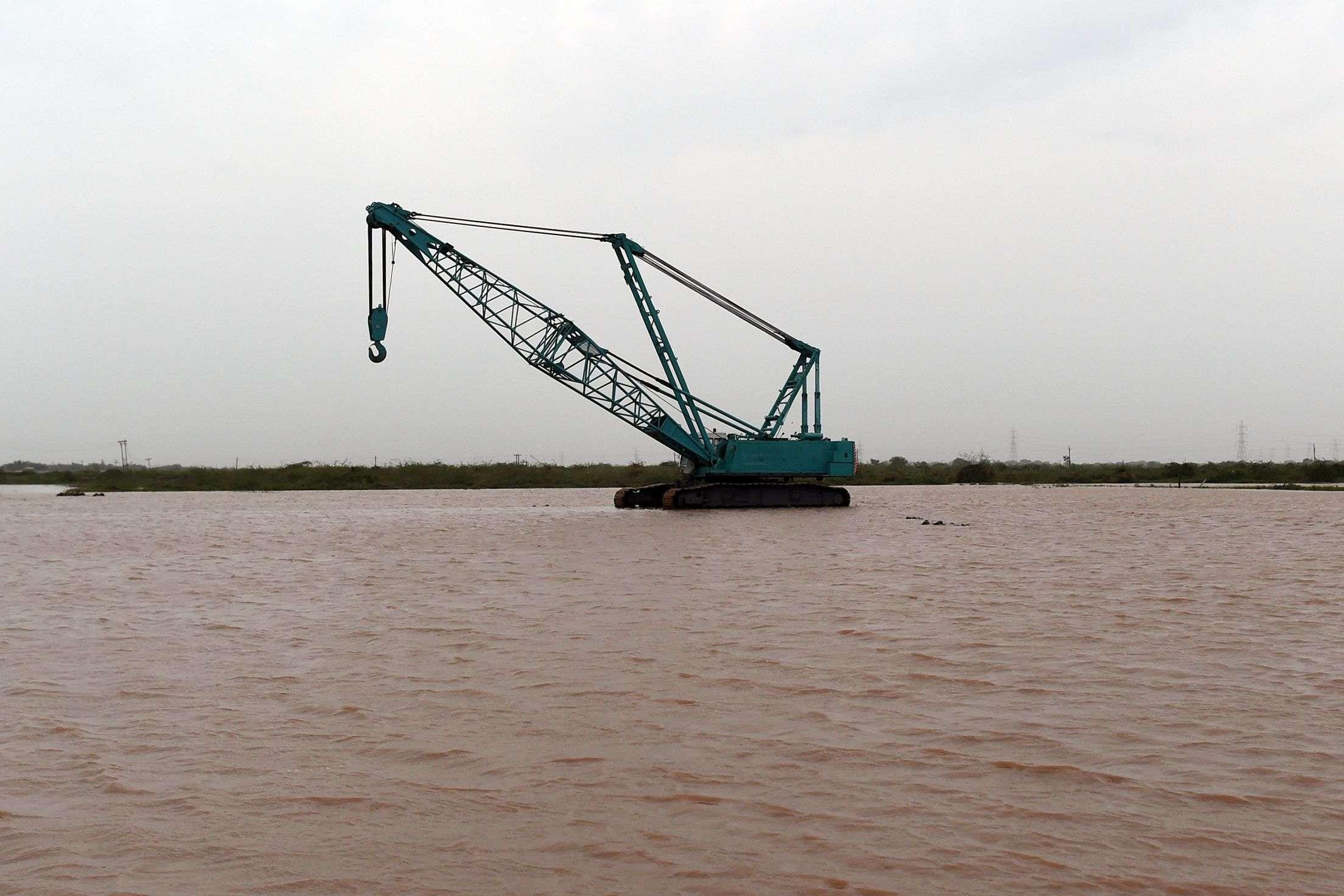 Une grue utilisée pour décharger les camions est perdue dans les eaux, à Maliya, dans le district de Morbi, à environ 200 kilomètres d'Ahmedabad.