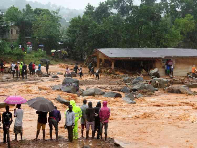 Des Sierra-Léonais regardent les dégâts causés par la coulée de boue dans la nuit du 13 au 14août à Freetown.