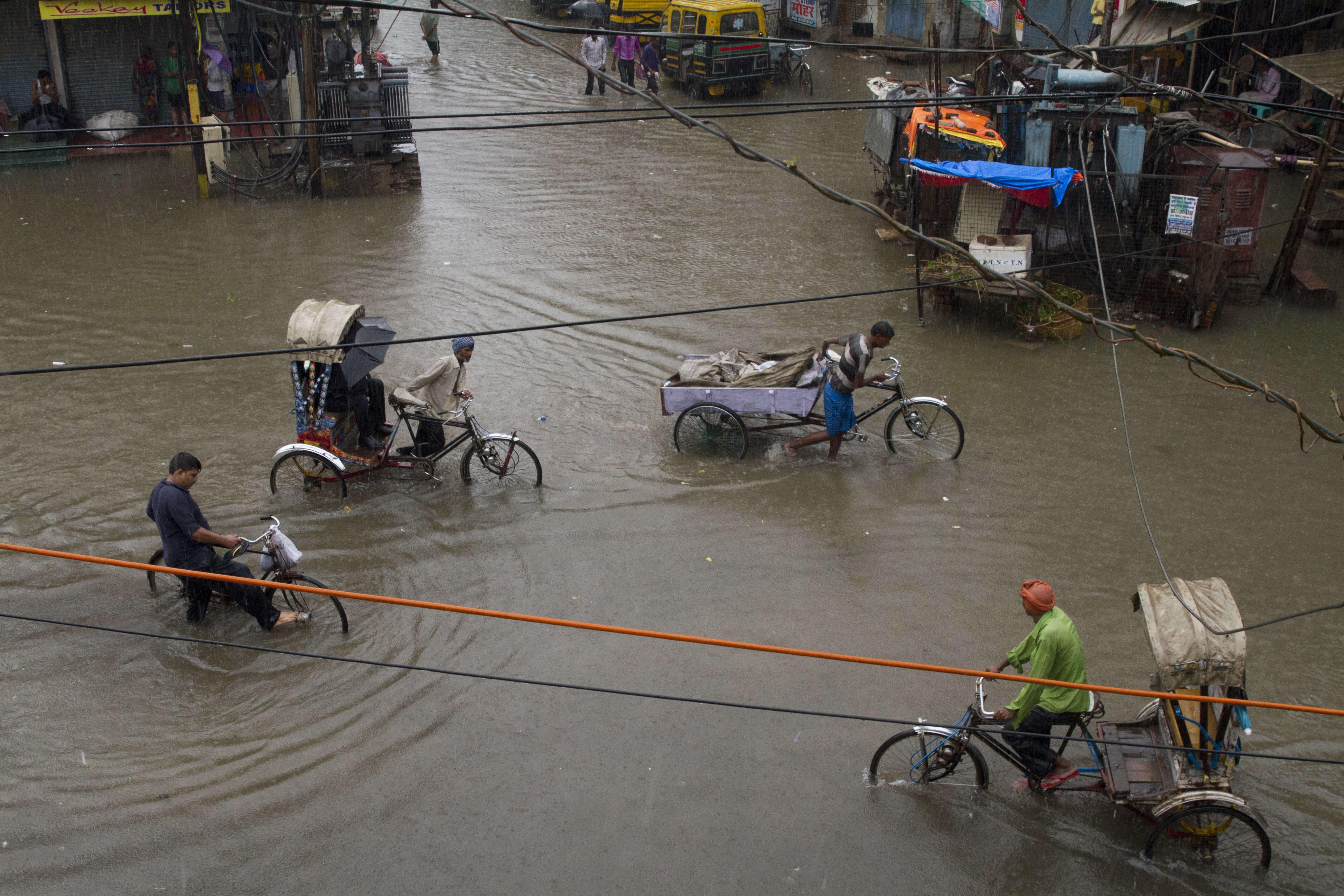 Des tireurs de pousse-pousse indiens traversent un carrefour inondé après de fortes pluies, à Allahabad.