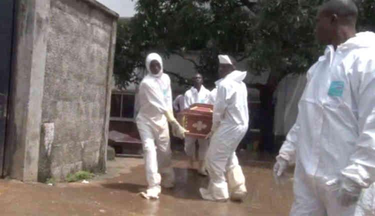 Le 15août, des hommes en combinaison de protection transportent un cercueil à l'hôpital Connaught, en Sierra Leone. Selon Sulaiman Zaino Parker, un responsable du conseil municipal de la capitale, environ 150personnes ont déjà été enterrées mardi soir à Freetown. De nombreuses autres victimes doivent être inhumées dans la localité proche de Waterloo.