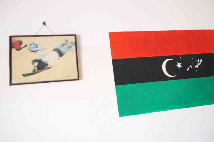 Le centre de détention pour migrants de Zaouia. Sur les murs du couloir d'entrée qui mène aux cellules sont exposées des photographies, encadrées. Elles montrent des corps inertes de personnes probablement mortes de soif dans le désert, à coté du drapeau libyen.