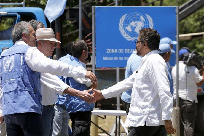 Le président colombien Juan Manuel Santos (deuxième à gauche) serre la main de l'un des leaders des FARCIvan Marquez sur le site de démobilisation de Fonseca, le 15août.