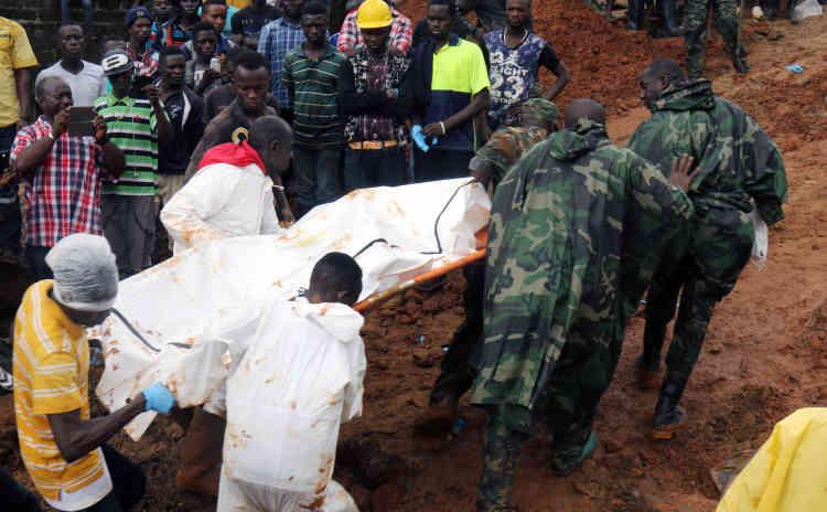 Des volontaires de la Croix-Rouge locale transportent un cadavre dans le quartier de Regent, en Sierra Leone, le 14août.