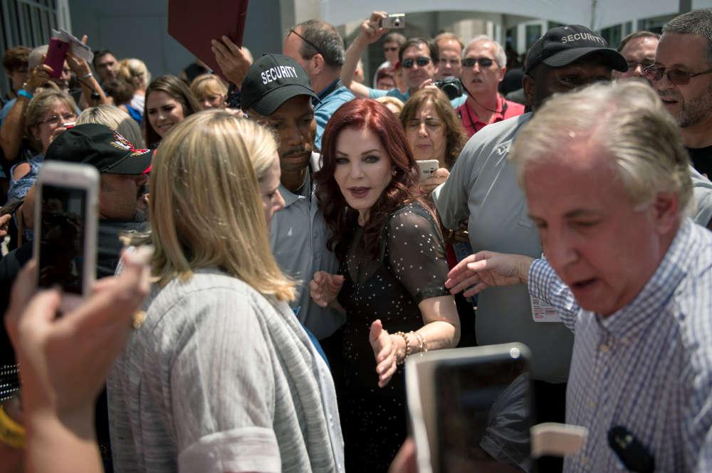 Priscilla Presley, l'ancienne épouse d'Elvis, est escortée par des agents de sécurité après avoir salué les fans venus visiter la maison de Memphis.